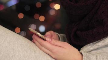 ragazza si siede sul davanzale della finestra e utilizza lo smartphone video