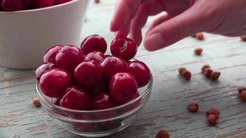 mão pegando cereja doce da tigela