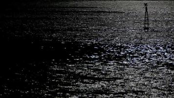 Reflection of moonlight sea with a lighted buoy.