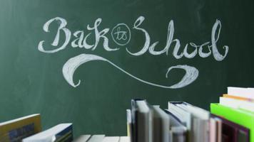 de volta às aulas escrito à mão no quadro-negro, livros em primeiro plano, filmado em r3d video
