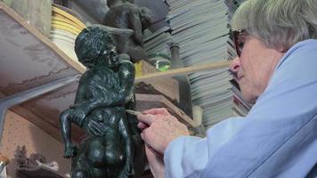 scultore che lavora alla sua statua