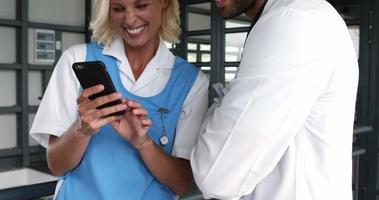 médecins souriants utilisant un smartphone