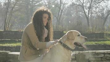 Mädchen und ihr Hund spielen in einem Park