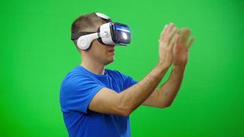 Man in a virtual reality mask looks around. Green screen.