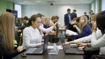 jovens alunas sentadas à mesa e se preparando para os jogos de negócios