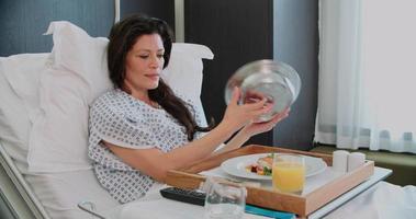 paziente nel letto di ospedale mangiare pasti e guardare la televisione