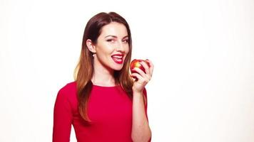 Mujer comiendo manzana roja sonriendo aislado sobre fondo blanco.
