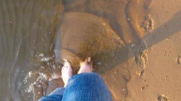 piernas completas mujer caminando por una playa de arena. la orilla arenosa del lago.