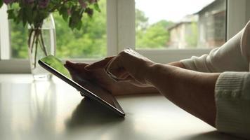Vue de côté: les mains d'une femme âgée à l'aide d'une tablette numérique à la maison video