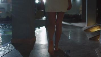 giovane donna attraente sta camminando lungo il bordo piscina in un asciugamano in un centro benessere termale.