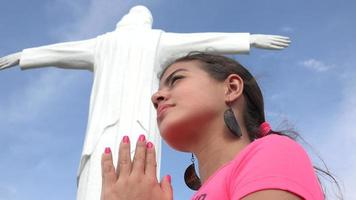 mujer rezando en estatua religiosa