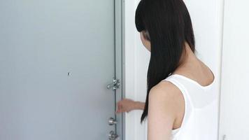 mujer joven cerrando la puerta