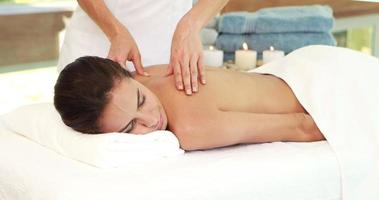 Masseuse giving massage to relax woman video