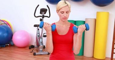 donna bionda sollevamento manubri sulla palla ginnica