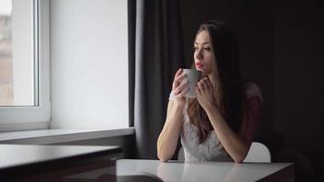 Jolie femme brune avec une tasse de café blanche