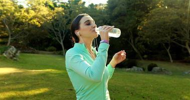 mulher bebendo água depois de correr no parque video