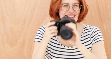 sorridente hipster donna di scattare una foto con la fotocamera