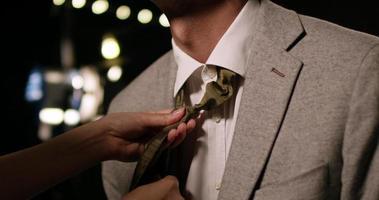 Frau, die die Krawatte des Mannes in der Studioumgebung bindet.