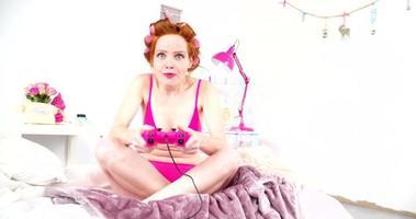mujer joven, juego, videojuegos, en cama