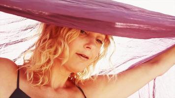 eine Frau, die am Strand mit einem Schal tanzt
