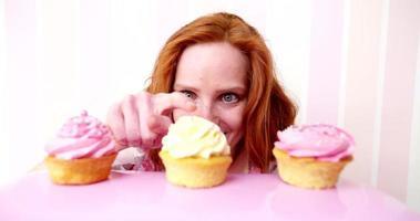 giovane donna dai capelli rossi vuole davvero mangiare cupcakes rosa