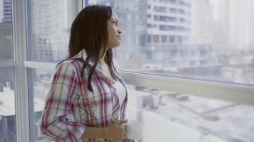 hispanische Frau in der städtischen Wohnung, die im Sofaschuss sitzt
