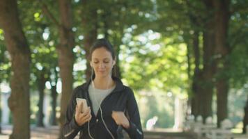 mujer joven y atractiva mediante teléfono móvil antes de correr al aire libre.