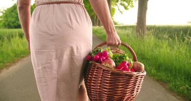 donna che tiene un cesto di verdure in un parco