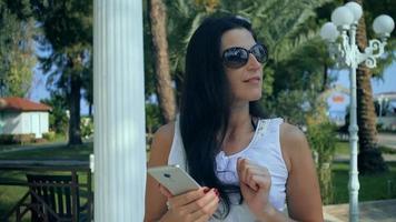 donna che digita sullo smartphone in giardino tropicale. vacanza video