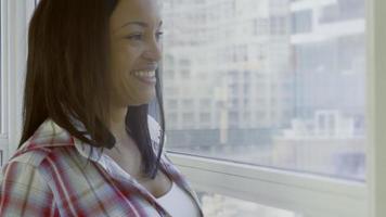 mulher hispânica em condomínio urbano olhando pela janela video