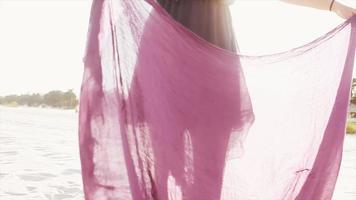 mujer bailando en la playa con una bufanda video