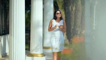 mulher digitando no smartphone no jardim tropical. período de férias