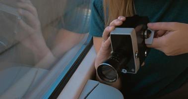 donna che utilizza retro videocamera per riprendere la strada