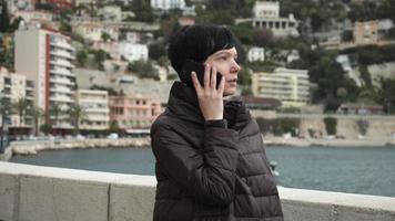 mujer en la ciudad a orillas del mar con smartphone