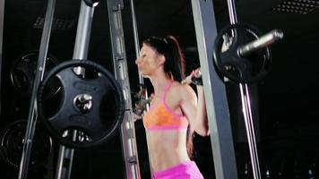 Athletic woman squats with a barbell. Motivation in sport video