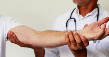 Arzt hilft seinem Patienten bei Übungen video