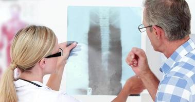 Arzt zeigt ihrer Patientin Röntgenbilder video