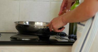 vrouw iets in de koekenpan op de kookplaat koken