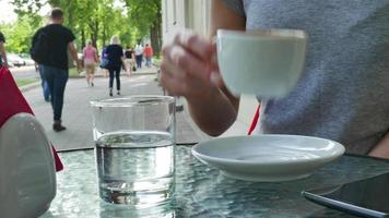 Woman drinking coffee. Glasses with water are nearby the cup video