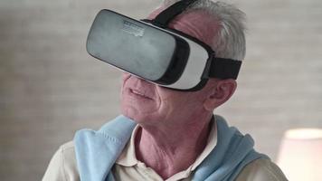 uomo anziano curioso guardandosi intorno in cuffia vr video