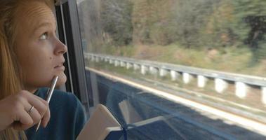 mulher fazendo anotações ou desenhando no trem video