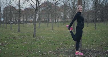 fit Frau mittleren Alters, die sich im Park ausdehnt