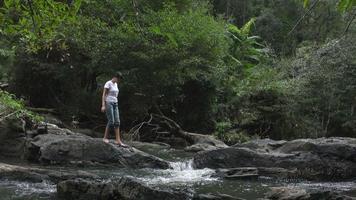 donna a piedi nudi che cammina sul fiume di montagna