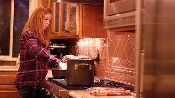 Eine Frau gießt etwas Tomatensauce in einen Topf video