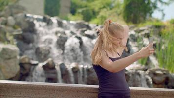 Woman selfie. Young woman taking selfie at park. Selfie woman taking photo video