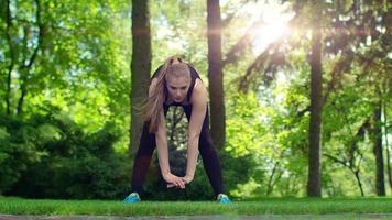 Frau, die sich am Morgen im Park ausdehnt. Frau im Freien trainieren video