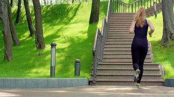 Woman running up stairs in slow motion. Fitness woman running upstairs