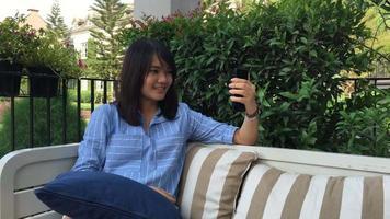 junge Frau, die Selbstporträt mit Smartphone macht. Mädchen macht Selfie. Frau im Café. Frau allein. Selbstporträt im Café im Freien.