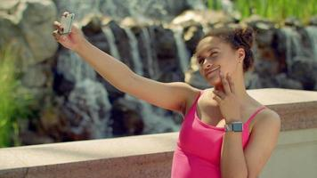 Young woman taking selfie and watch photo on smartphone video