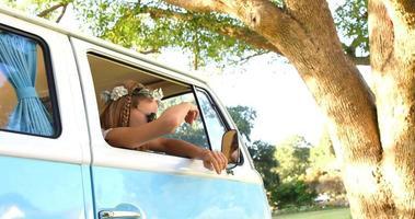 mulher hipster olhando pela janela da van